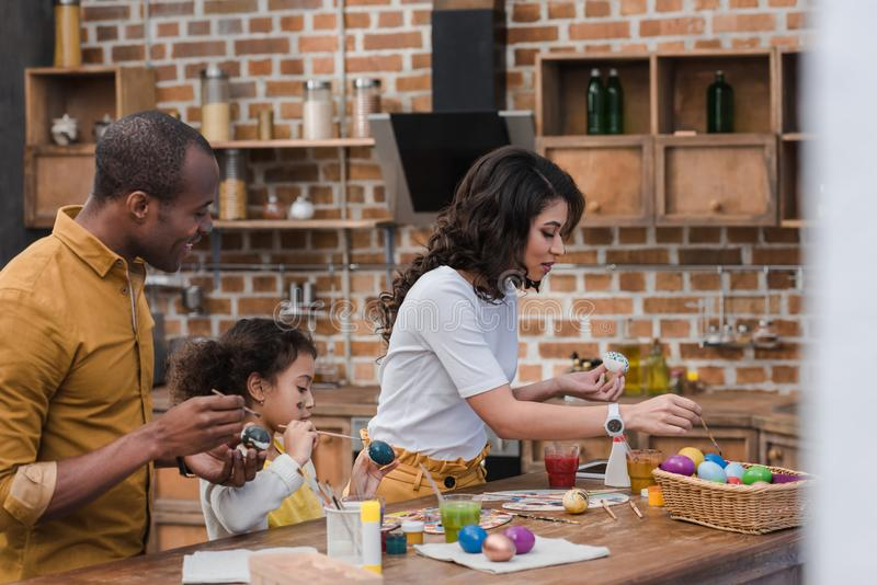 African american parents and daughter painting easter eggs together on kitchen. Happy african american parents and daughter painting easter eggs together on stock photography