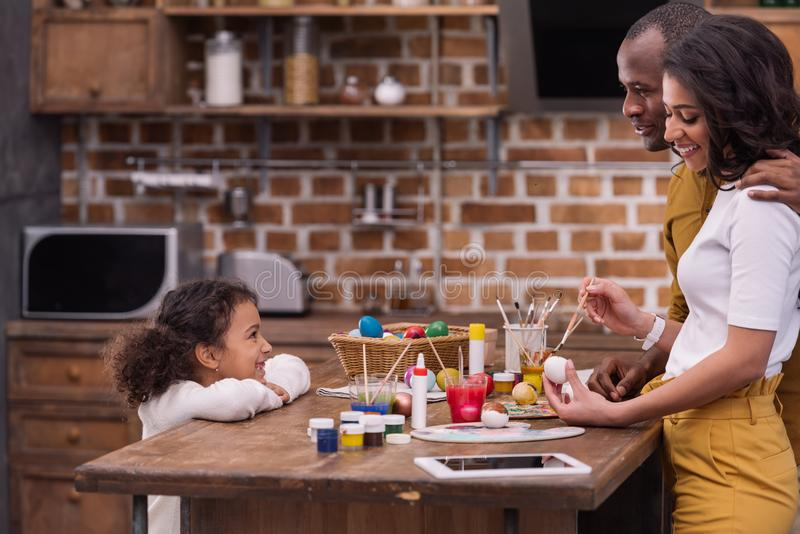 African american parents painting easter eggs at kitchen. Side view of african american parents painting easter eggs at kitchen stock image