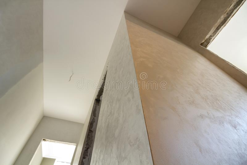 Angled view of new unfinished apartment under reconstruction. White ceiling, plastered walls, doors openings. Construction and. Reconstruction concept royalty free stock image