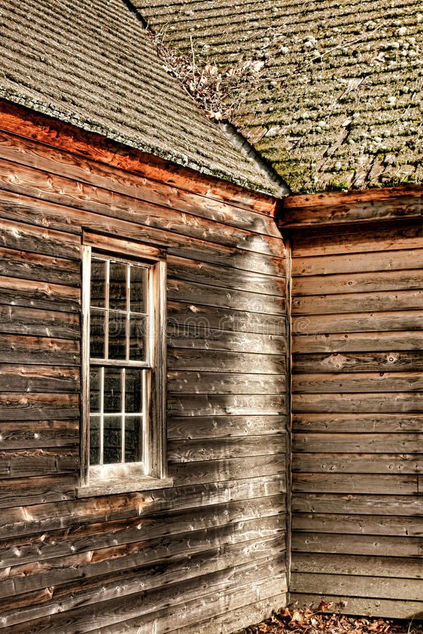 Antique Farmhouse Old Window and Clapboard Siding. Old historic farm building with wood sash window and exposed clapboard siding outside walls under an antique stock photography