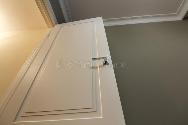 Apartment after renovation interior. White door with metal handle, light walls and ceiling, angle view.  stock photography