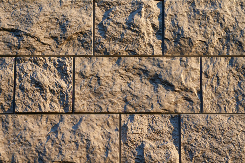 Artificial stone finishing. Artificial stone textured finishing on the foundation of the house stock photo
