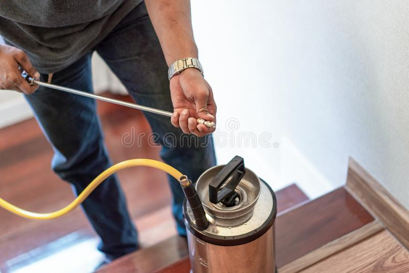 Asian Thailand termite staff company is spraying the destroy chemical liquid in to white ant nest in the wood around human house. Asian Thailand termite staff royalty free stock photography