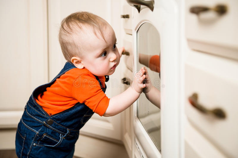 Baby watching inside kitchen oven. Curious baby watching through glass of kitchen oven royalty free stock images