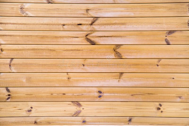 Background of planed larch planks, thermo clapboard, with a beautiful pattern of the structure of trees with knots. Design backgro. Unds texture construction royalty free stock photography