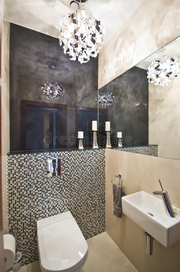 Bathroom. Interior of an elegant little bathroom with sink, toilet, mirrors and decorative chandelier. Grey white and black color scheme royalty free stock images