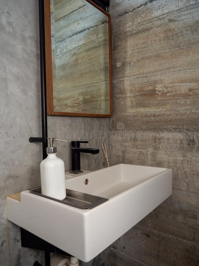 Bathroom modern loft style. White bathroom sink with faucet with liquid soap bottle and mirror on concrete wall. Vertical style stock photos