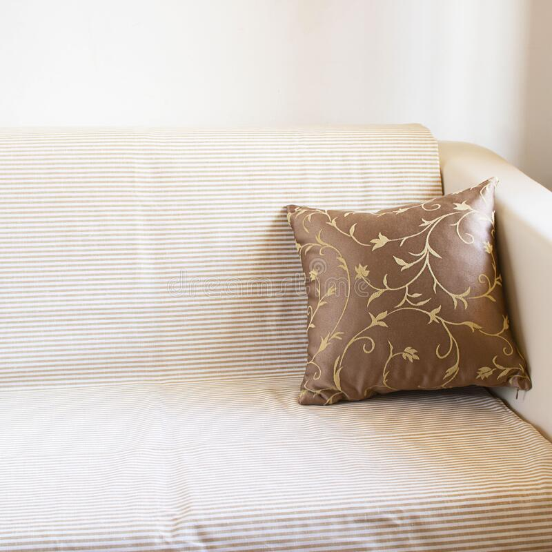 Beautiful brown pillow on light sofa covered by linen blancet with pale stripes on the background of white wall. Decoration in. Beautiful brown pillow on light stock image