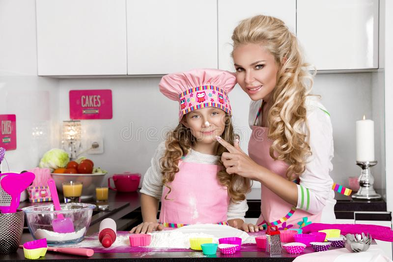 Beautiful stunning woman mother and daughter in aprons kitchen cooking in the kitchen cookies stock image