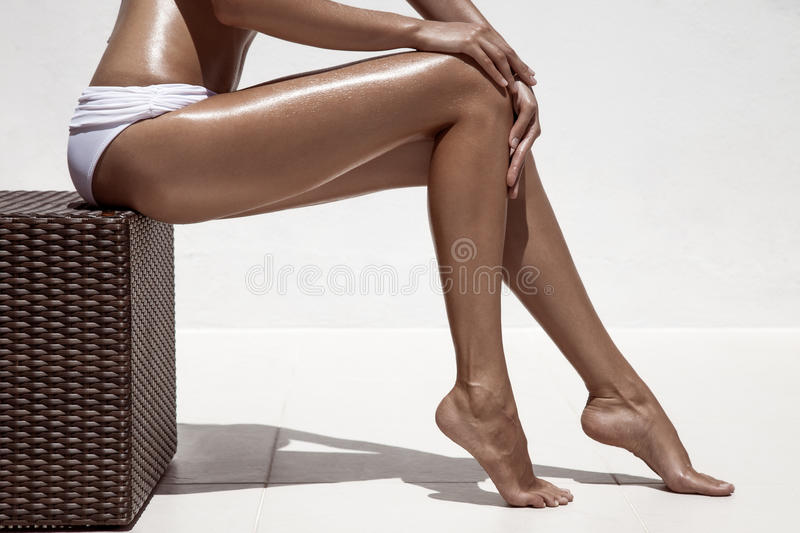 Beautiful woman tan legs. Against white wall. stock image