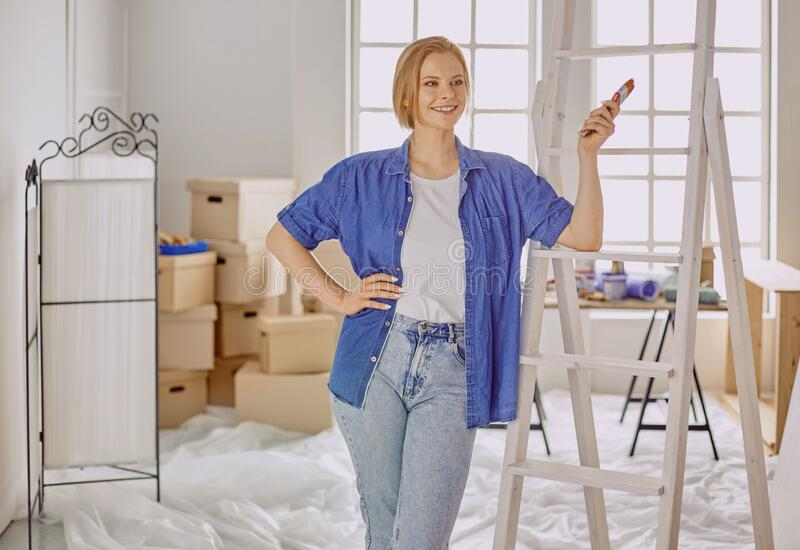 Beautiful young woman on a white wooden stepladder. Ready to repair the room. Women housework concept.  royalty free stock photography