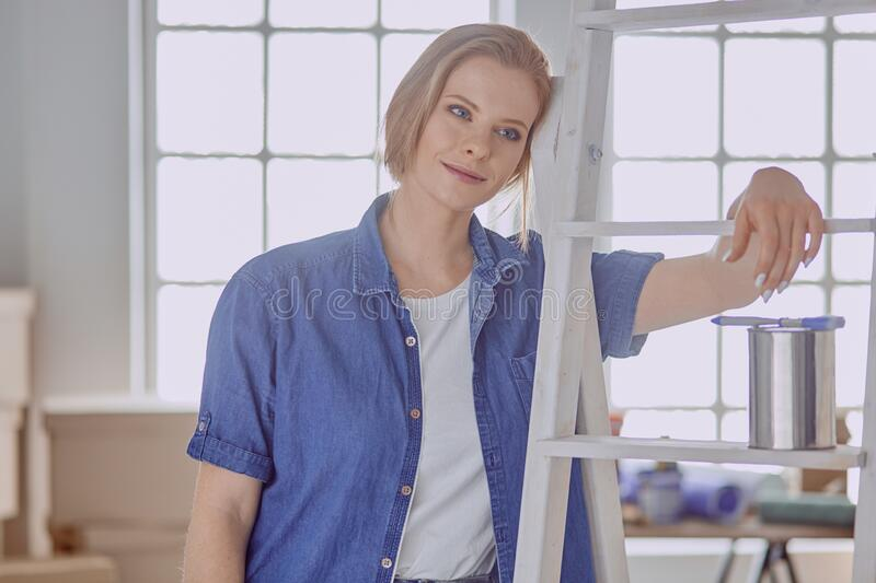 Beautiful young woman on a white wooden stepladder. Ready to repair the room. Women housework concept.  royalty free stock image