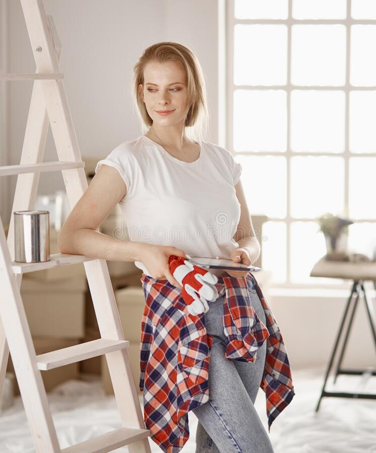 Beautiful young woman on a white wooden stepladder. Ready to repair the room. Women housework concept.  royalty free stock photo