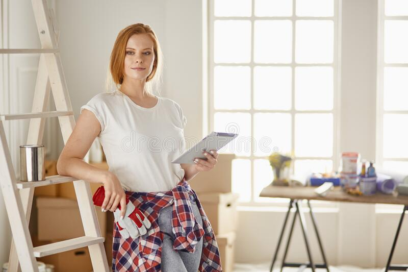 Beautiful young woman on a white wooden stepladder. Ready to repair the room. Women housework concept.  stock photo