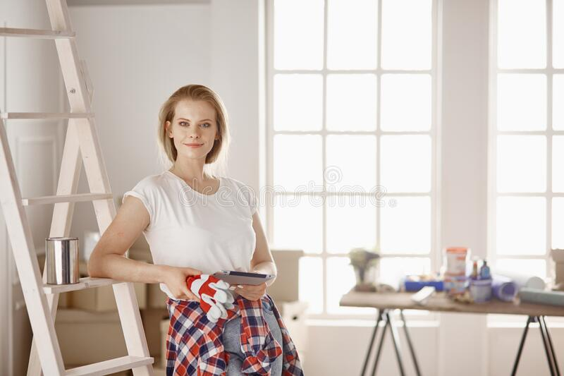 Beautiful young woman on a white wooden stepladder. Ready to repair the room. Women housework concept.  stock images
