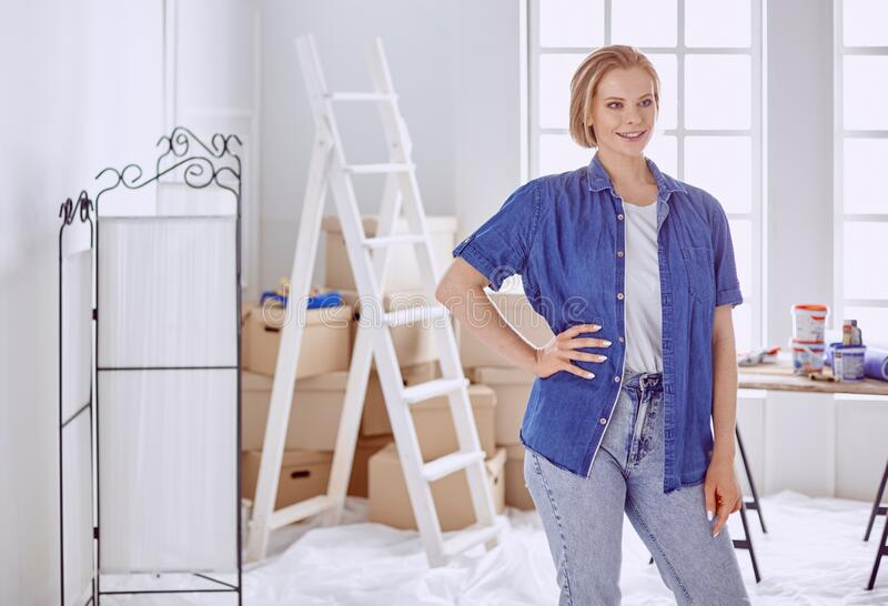 Beautiful young woman on a white wooden stepladder. Ready to repair the room. Women housework concept.  royalty free stock photos
