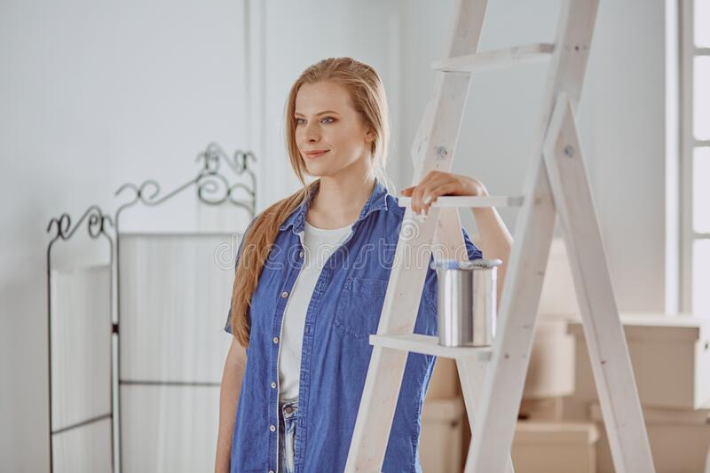 Beautiful young woman on a white wooden stepladder. Ready to repair the room. Women housework concept royalty free stock photography