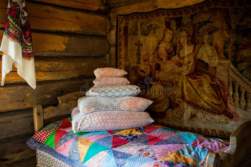 Made bed. bedroom. Interior of an old Russian hut Bed in a Russian hut. Interior items with ancient utensils Old Russian life. Bed in a Russian hut. Interior royalty free stock images
