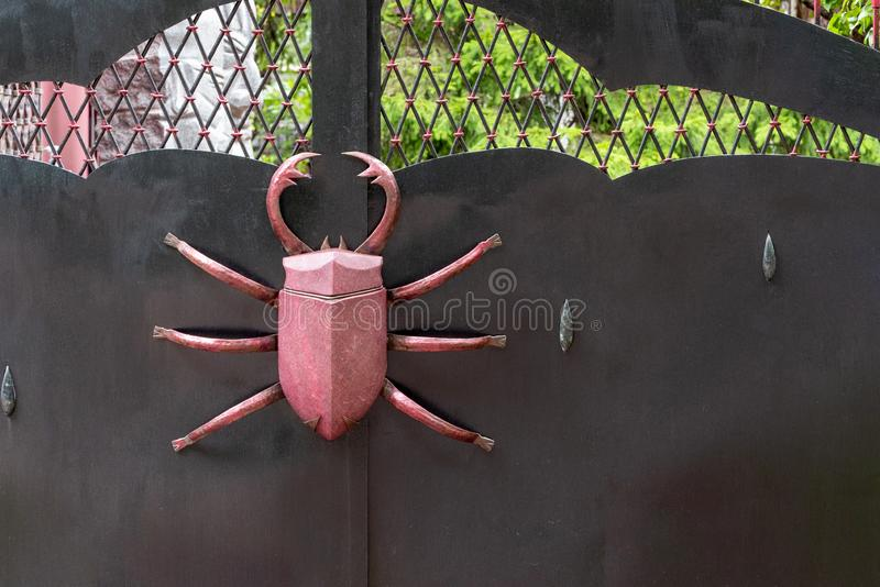 Black metal gate with a large decorative beetle. Space for lettering or design.  royalty free stock images
