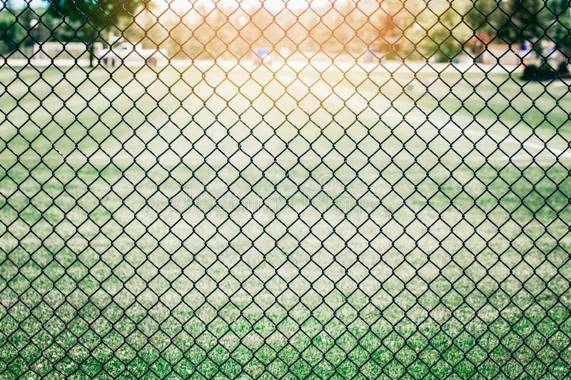 Black metal netting wire mesh fence against green field meadow. Texture pattern surface background. Closeup of black metal netting wire mesh fence against green stock photos
