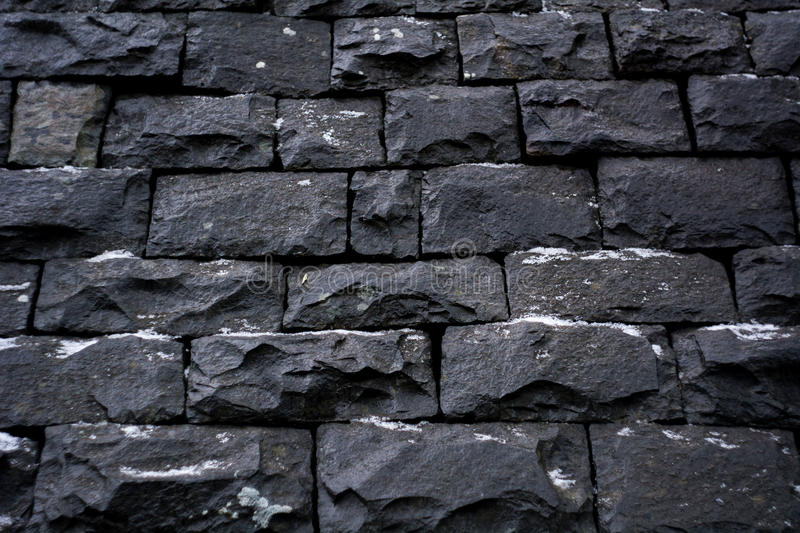 Black stone wall background texture. Black stone wall with snowe winternlair digital texture wall brick build brickwork color backdrop massive structure stock photography