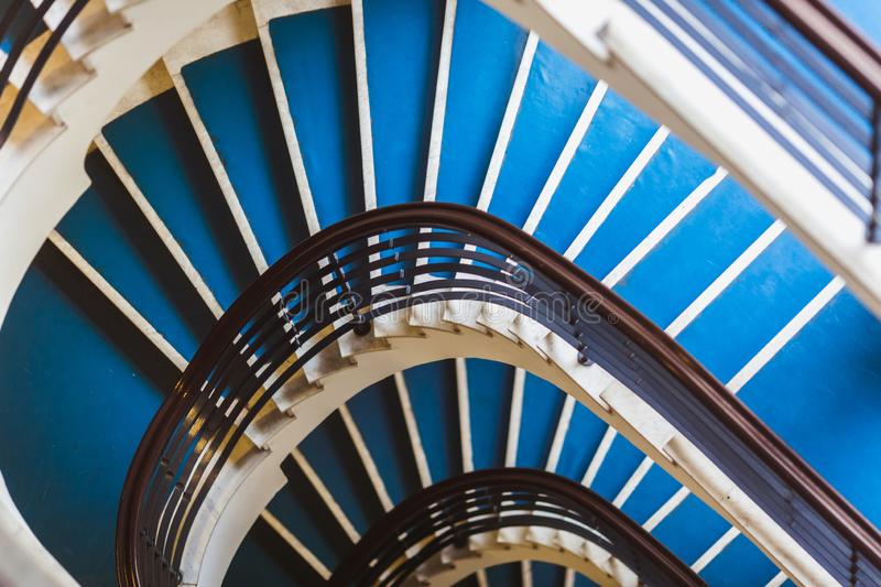 Blue background made for Old blue spiral staircase inside an old house. Color 2020. royalty free stock photo
