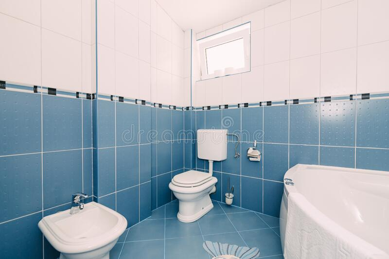 Bellagio, Italy - 07 june 2020: A blue bathroom with a toilet, sink, bathtub and a window open for ventilation. A blue bathroom with a toilet, sink, bathtub and stock images
