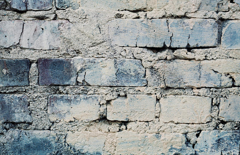 Blue brick wall with cracks and scuffs, urban loft background. Aged blue brick wall with cracks and scuffs, urban loft background royalty free stock images