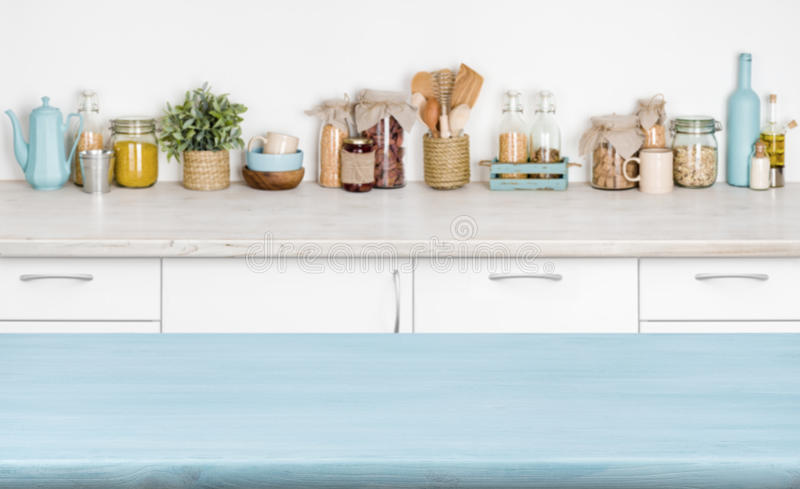 Blue empty wooden kitchen table over blurred food ingredients background stock photography