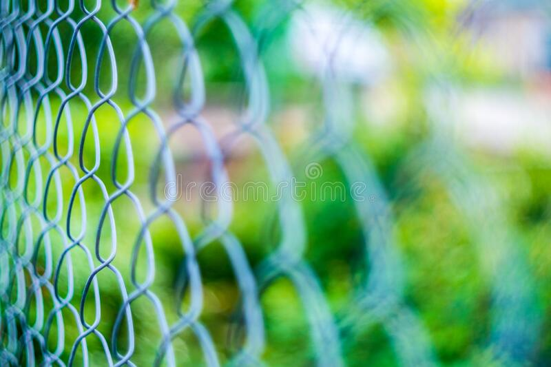 Metal mesh netting. Green blurred background. Bright colored bokeh.  stock photography