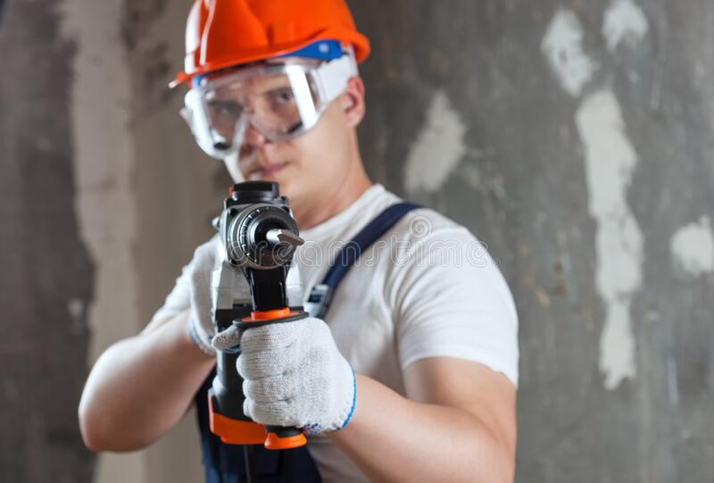 The builder with hammer drill perforator equipment making hole in wall at construction site. Repair work, interior decoration of stock image