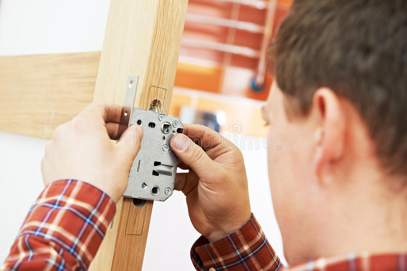 Carpenter at door installation. Male handyman carpenter at interior wood door lock installation with angle royalty free stock photo