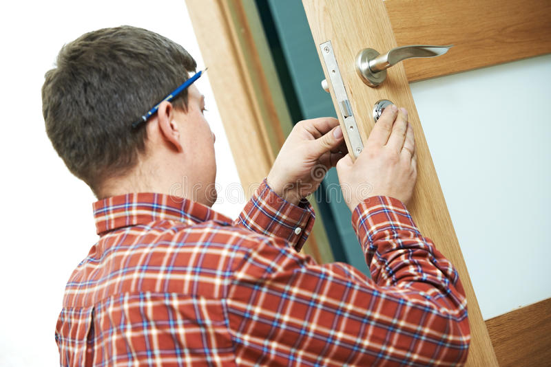 Carpenter at door lock installation. Male handyman carpenter at interior wood door lock installation stock photography