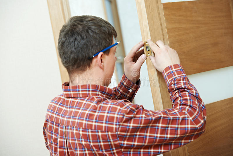 Carpenter at door lock installation. Male handyman carpenter at interior wood door lock installation royalty free stock image
