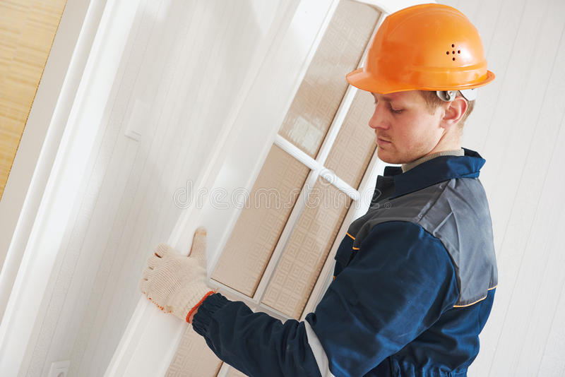 Carpenter worker at door installation. Male carpenter builder worker at interior wood door installation stock images