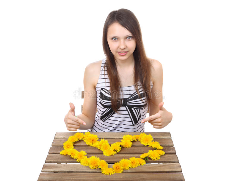 Caucasian teen girl, 15 years old, shows a yellow. Caucasian teen girl, brunette, 15 years old, shows a yellow valentine made from dandelion flowers on the table royalty free stock photography