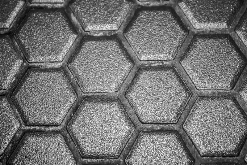 Ceramic tiles mosaic made of gray rhombuses, without grouting, the mesh-base and glue is visible. The concept of repair. Background stock image