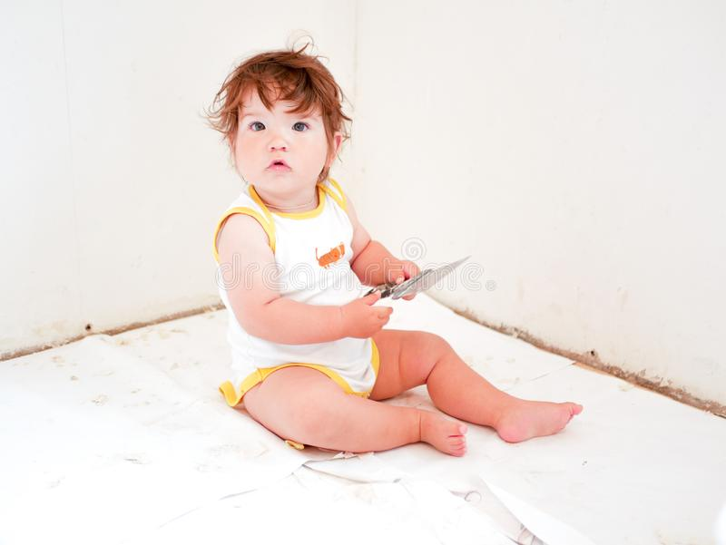 A child with a spatula son helps to make repairs. child with a working look. repair room concept. repair com royalty free stock images