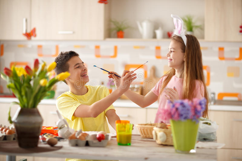 Children having fun in kitchen while painting Easter eggs. Happy male and female child in kitchen having fun while painting Easter eggs royalty free stock image