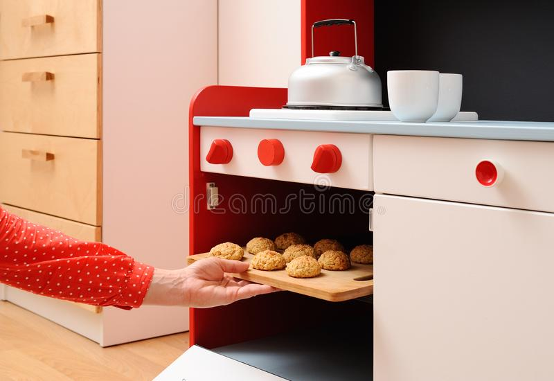Children play in kitchen. Baking homemade cookies in toy oven. Closeup stock image