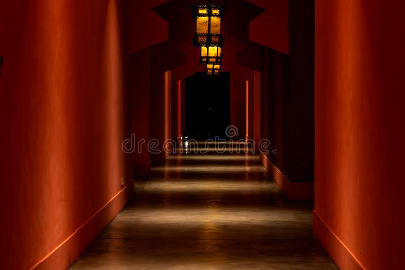 Chinese style hotel corridor with many doors and red walls on both sides and chinese lanterns illuminated lanterns leading into stock images