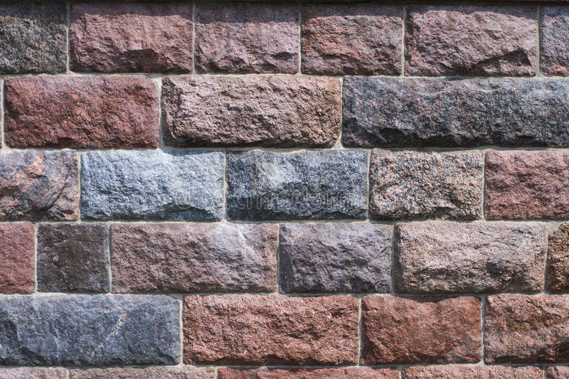 Chipped stone wall background. A background picture of rough reddish grayinsh chipped granite stone wall stock photos