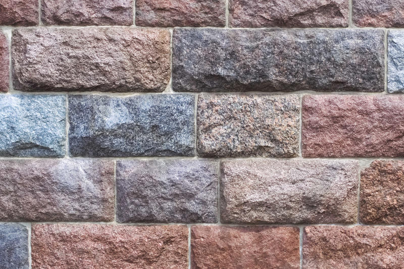 Chipped stone wall background. A background picture of rough reddish grayinsh chipped granite stone wall stock image