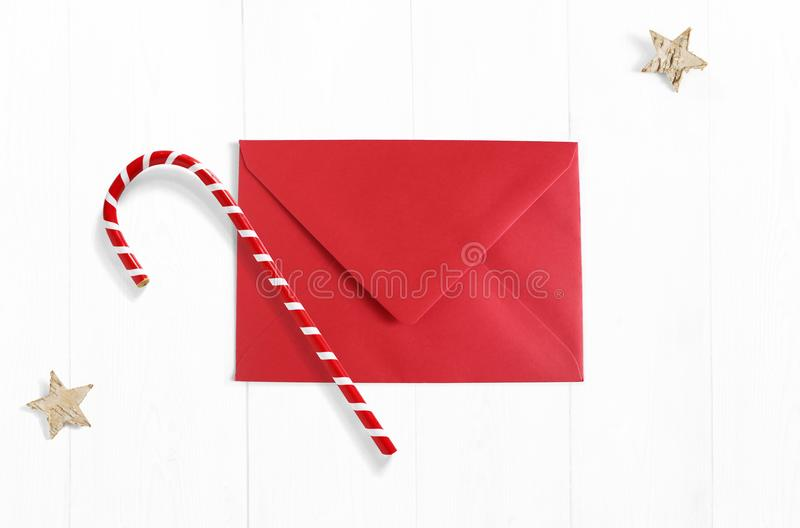 Christmas mockup scene with red envelope, candy cane decoration and stars made of birch bark on white wooden background. Empty space for your text. Top view royalty free stock image