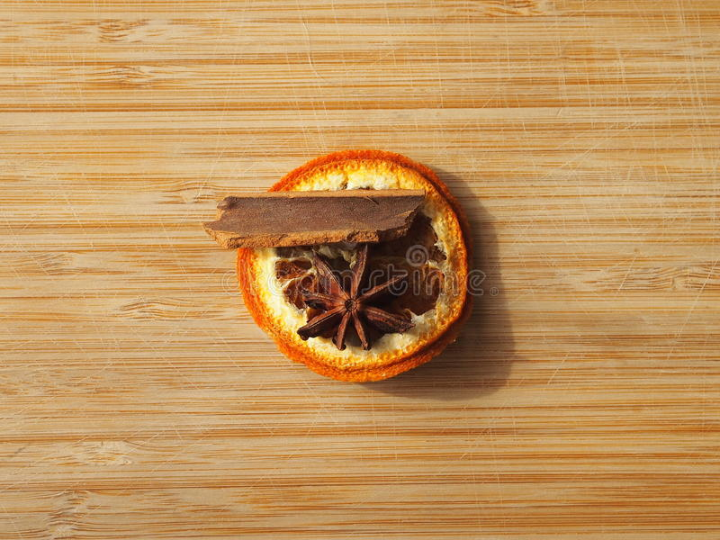 Christmas tree decoration - dry orange peel, with a cinnamon bark and a piece of star anise. Bamboo wood background royalty free stock image