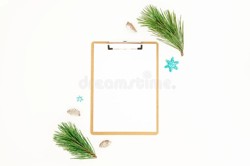 Christmas winter concept with clipboard, evergreen pine branches and coneson white background. Flat lay, top view. New Year royalty free stock photos