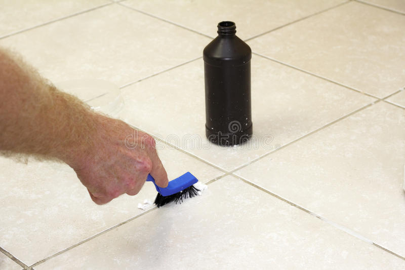 Cleaning Floor Grout with Baking Soda. Hand with a blue handled black scrub brush cleaning grout with baking soda and peroxide. Floor grout tile being cleaned royalty free stock photography