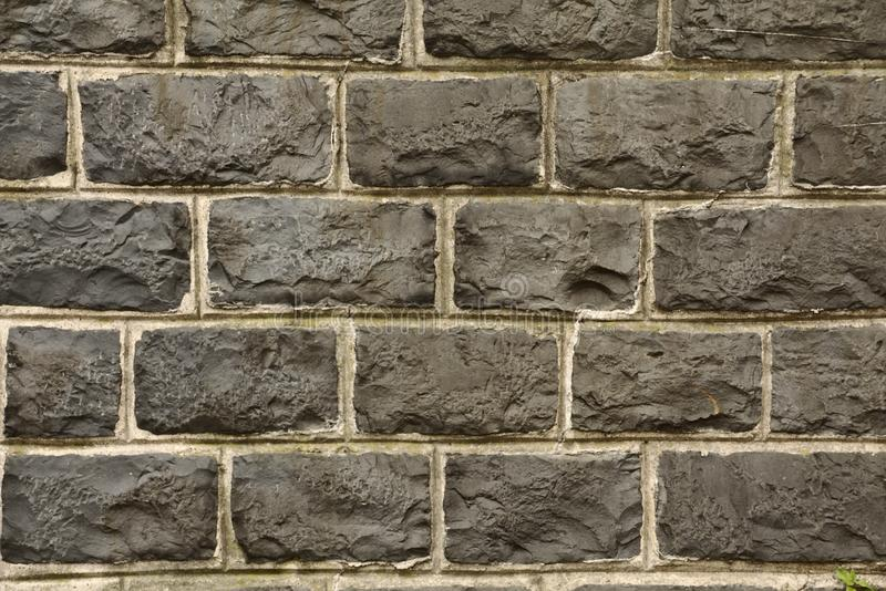 Black natural stone wall. Close up an details of a black natural stone wall with white lines stock photo