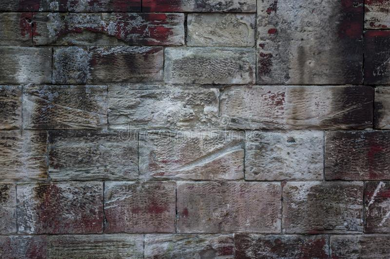 Close-up of an old weathered sandstone wall of different sized s. Tones and texture with efflorescence and red, white and black spots of color stock images