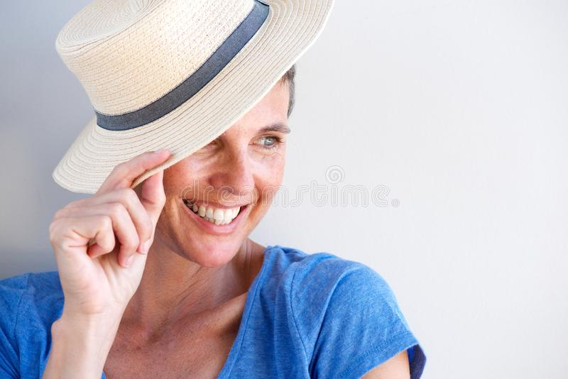 Close up beautiful mature woman smiling with hat against white wall royalty free stock image